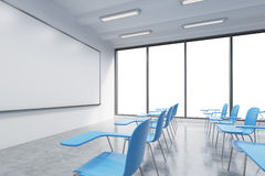 A classroom or presentation room in a modern university or fancy office. Blue chairs, a whiteboard on the wall and panoramic windo Stock Image