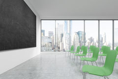 A classroom or presentation room in a modern university or fancy office. Green chairs, a black chalkboard on the wall and panorami Stock Image