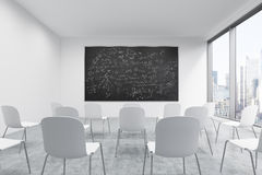 A classroom or presentation room in a modern university or fancy office. White chairs, a black chalkboard with math formulas on th Royalty Free Stock Photos
