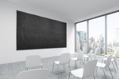 A classroom or presentation room in a modern university or fancy office. White chairs, a black chalkboard on the wall and panorami Royalty Free Stock Images