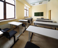Classroom with wooden school desks and chairs Stock Image