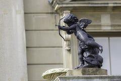 Classsical cherub statue. A traditional classical statue of a cherub firing an arrow. A symbol of love Royalty Free Stock Photo