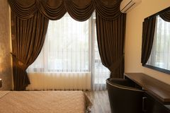 Classy bedroom interior design. Large bed. Room with brown color tone furniture. Windows with long curtains, drapery and sheers. Interior photography stock photo