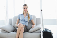 Classy blonde businesswoman waiting sitting on couch next to her suitcase Royalty Free Stock Images
