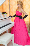 Classy blonde in long red dress is standing next to the  piano. Classy blonde in long red dress is standing next to the piano Royalty Free Stock Photography