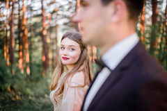 Classy bride with red lips admires handsome groom. While standing between high trees stock image