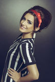 Classy brunette woman in retro attire. Classy brunette young woman in retro black-and-white stripped attire, accessorized with red headband and 60s hairdo Royalty Free Stock Image