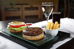 Classy Burger. A classic burger on a luxory table Royalty Free Stock Photo