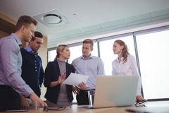 Classy business colleagues discussing around desk. In meeting room Royalty Free Stock Photos