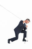 Classy businessman pulling a rope. On white background royalty free stock photo