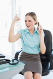 Classy businesswoman on the phone cheering with raised arms Royalty Free Stock Photo