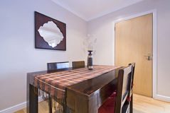 Classy dining area. With a dining table and chairs made of massive wood Stock Images