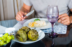 Classy dinner table setting, cooked artichokes sitting in middle, mans arms visible holding cutlery next to white plate Stock Photos