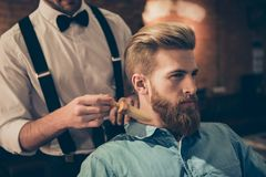 Classy dressed barber shop hairdresser is cleaning client`s neck. With a brush and presents his work for him. Stunning! Hairdo looks trendy and so perfect stock photo