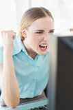 Classy excited businesswoman sitting in front of computer Stock Photo