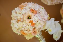 Classy floral arrangement in a pastel round bouquet featuring pink hydrangea roses and orchids. Set on an elegant glass support as a centerpiece for a wedding stock photos