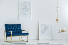 Classy furniture in luxurious interior. Classy furniture and framed map posters on a white wall in a luxurious, designer living room interior with minimalist Stock Photography