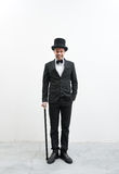Classy gentleman. Classy smiling gentleman standing on white background and concrete floor in elegant suit with cane and bowler hat Stock Image