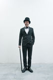 Classy gentleman. Classy smiling gentleman standing on white background and concrete floor in elegant suit with cane and bowler hat Royalty Free Stock Image