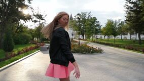 Classy girl dressed in pink skirt turning in the park in slow motion