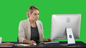 Classy happy businesswoman working at computer on a Green Screen, Chroma Key.
