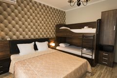 Classy hotel bedroom interior design. Large bed, bunk-beds. Family room with brown color tone furniture.  stock photography