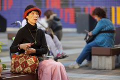 Classy Japanese lady. OSAKA, JAPAN, NOVEMBER 13, 2011 : A well dressed classy lady is sitting on a bench in a city square of Osaka, Japan royalty free stock photo