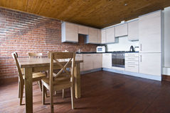 Classy kitchen and dining area. With wooden table, chairs and floor Stock Photography