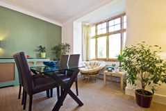 Classy living area with dining table. For four and rattan armchair with coffee table Stock Photo