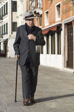 Classy old man walking in Venice. Royalty Free Stock Images