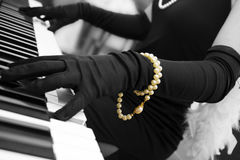 Classy Piano. A classy woman in vintage gloves playing piano royalty free stock photo