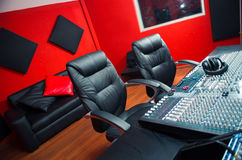 Classy professional recording studio setup, large desk with mixing console and two chairs, window for vocal booth, sofa. Placed behind Royalty Free Stock Photo