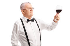 Classy senior gentleman looking at a glass of red wine Royalty Free Stock Images