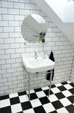 Classy toilet. Furnished toilet in a classy, minimalistic style. Black and white tiles. Compostable bamboo toth brush and a Hyacint on the shelf royalty free stock photography