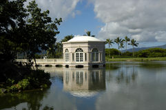 Classy Wedding Location. Wedding chapel is reflected in the still waters of a lagoon on Kauai, Hawaii.  Blue skies which are also reflected in the waters.  Palm Royalty Free Stock Photography