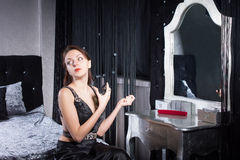Classy Woman in Black Spraying Perfume Stock Photo