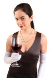 Classy Woman Holding a Glass of Red Wine. A beautiful woman in a classy dress is holding a glass of red wine royalty free stock photos