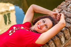 Classy woman lying on bridge. Classy woman with arms over head lying on ancient brick bridge near water canal Stock Images