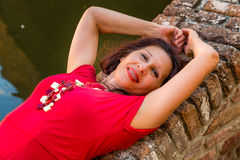 Classy woman lying on bridge. Classy woman with arms over head lying on ancient brick bridge near water canal Stock Image