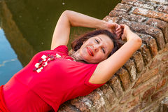 Classy woman lying on bridge. Classy woman with arms over head lying on ancient brick bridge near water canal Royalty Free Stock Images