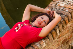 Classy woman lying on bridge. Classy woman with arms over head lying on ancient brick bridge near water canal Royalty Free Stock Image