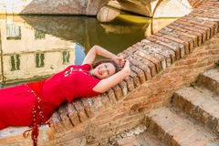 Classy woman lying on bridge. Classy woman with arms over head sitting on ancient bridge in Comacchio, a village you must visit in Italy, also called The Little Stock Images
