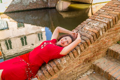 Classy woman lying on bridge. Classy woman with arms over head sitting on ancient bridge in Comacchio, a village you must visit in Italy, also called The Little Royalty Free Stock Photos