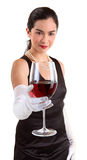 Classy Woman Serving a Glass of Red Wine. A beautiful woman in a classy dress is serving a glass of red wine royalty free stock photography
