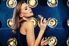 A classy woman singing in studio with a retro silver microphone. Mid side shot of a classy woman singing in studio with a retro silver microphone on spotlights stock photos