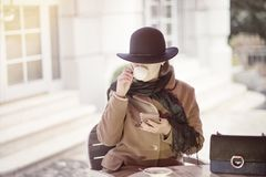 Classy woman sitting outdoors cafe with cell phone Stock Photo