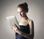 Classy woman using a tablet. A classy woman using a tablet royalty free stock photo