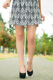 Classy woman visible from waist down wearing. Fashionable skirt and elegant black high heels walking on pavement, green park environment background Stock Photos