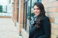 Classy woman wearing dark coat and black white. Clothing urban environment standing with back against brick wall smiling to camera Stock Images