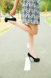 Classy woman wearing fashionable skirt and elegant. Black high heels bending right knee lifting shoe with hand Royalty Free Stock Images
